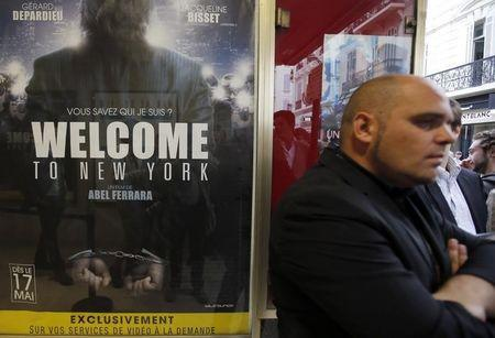 """A man stands next to a poster of the film """"Welcome to New York"""" directed by Abel Ferrara at a movie theatre ahead of a premiere screening during the 67th Cannes Film Festival in Cannes"""