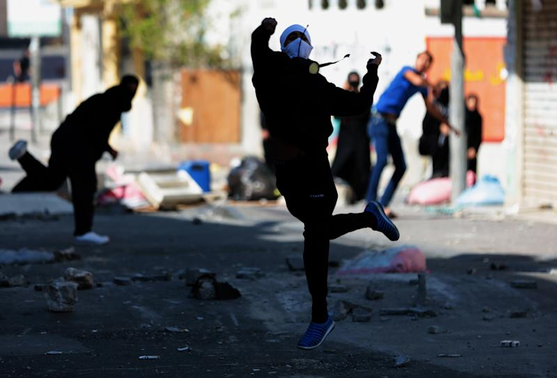 A Bahraini anti-government protester throws a stone toward riot police firing tear gas during clashes in Dih, on the edge of the capital of Manama, Bahrain, Friday, Feb. 14, 2014. An explosion rocked a bus carrying police in Bahrain on Friday, while security forces used tear gas in clashes with anti-government protesters on the third anniversary of an uprising in the small Gulf island nation. (AP Photo/Hasan Jamali)