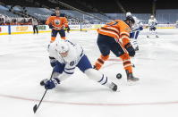Edmonton Oilers' Tyson Barrie (22) and Toronto Maple Leafs' John Tavares (91) battle for the puck during first-period NHL hockey game action in Edmonton, Alberta, Monday, March 1, 2021. (Jason Franson/The Canadian Press via AP)