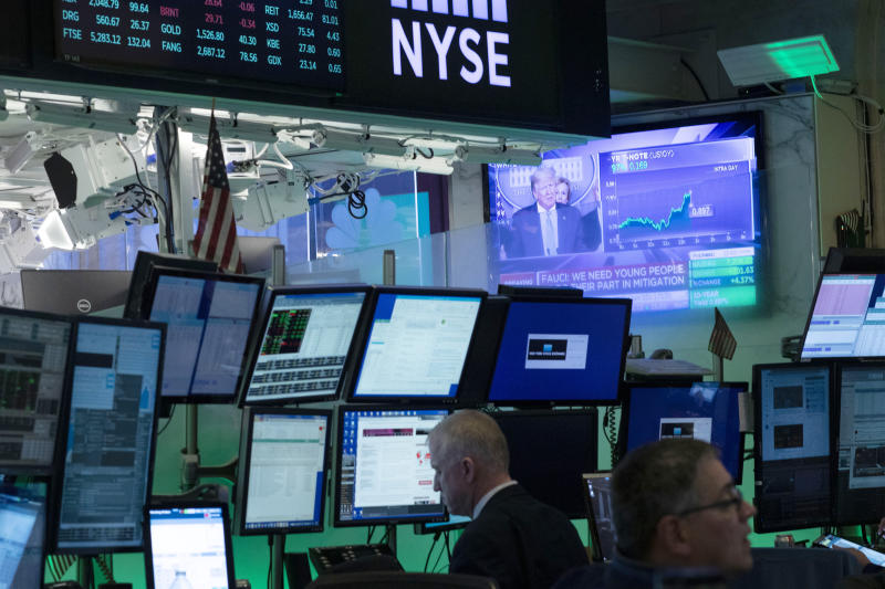 Traders at the New York Stock Exchange listen to President Donald Trump's televised White House news conference, Tuesday, March 17, 2020 in New York. Stocks are adding sharply to their gains on Wall Street after the president and his team announced more measures to combat the coronavirus outbreak. (AP Photo/Mark Lennihan)