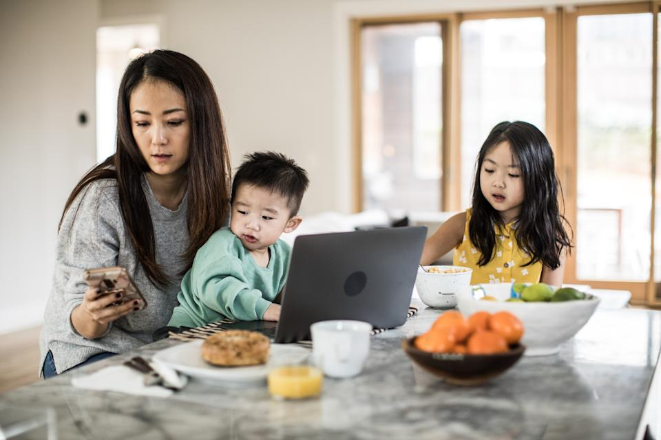 Mother multi-tasking with young children in kitchen table
