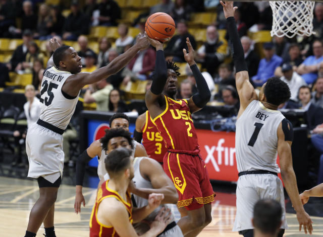 Southern California guard Jonah Mathews, center, drives to the basket between Colorado guards McKinley Wright IV, left, and Tyler Bey in the first half of an NCAA college basketball game Saturday, March 9, 2019, in Boulder, Colo. (AP Photo/David Zalubowski)