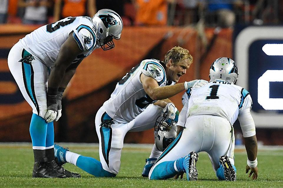 Teammates check on Panthers QB Cam Newton (1) after he was pummeled by a Broncos linebacker on Thursday. (Helen H. Richardson/Getty Images)