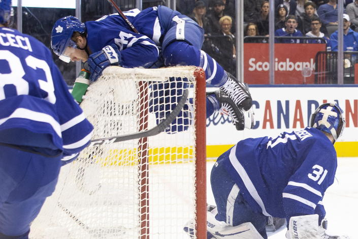 Toronto Maple Leafs defenseman Morgan Rielly (44) collides with the net behind goaltender Frederik Andersen (31) during the second period of the team's NHL hockey game against the Tampa Bay Lightning on Tuesday, March 10, 2020, in Toronto. (Chris Young/The Canadian Press via AP)