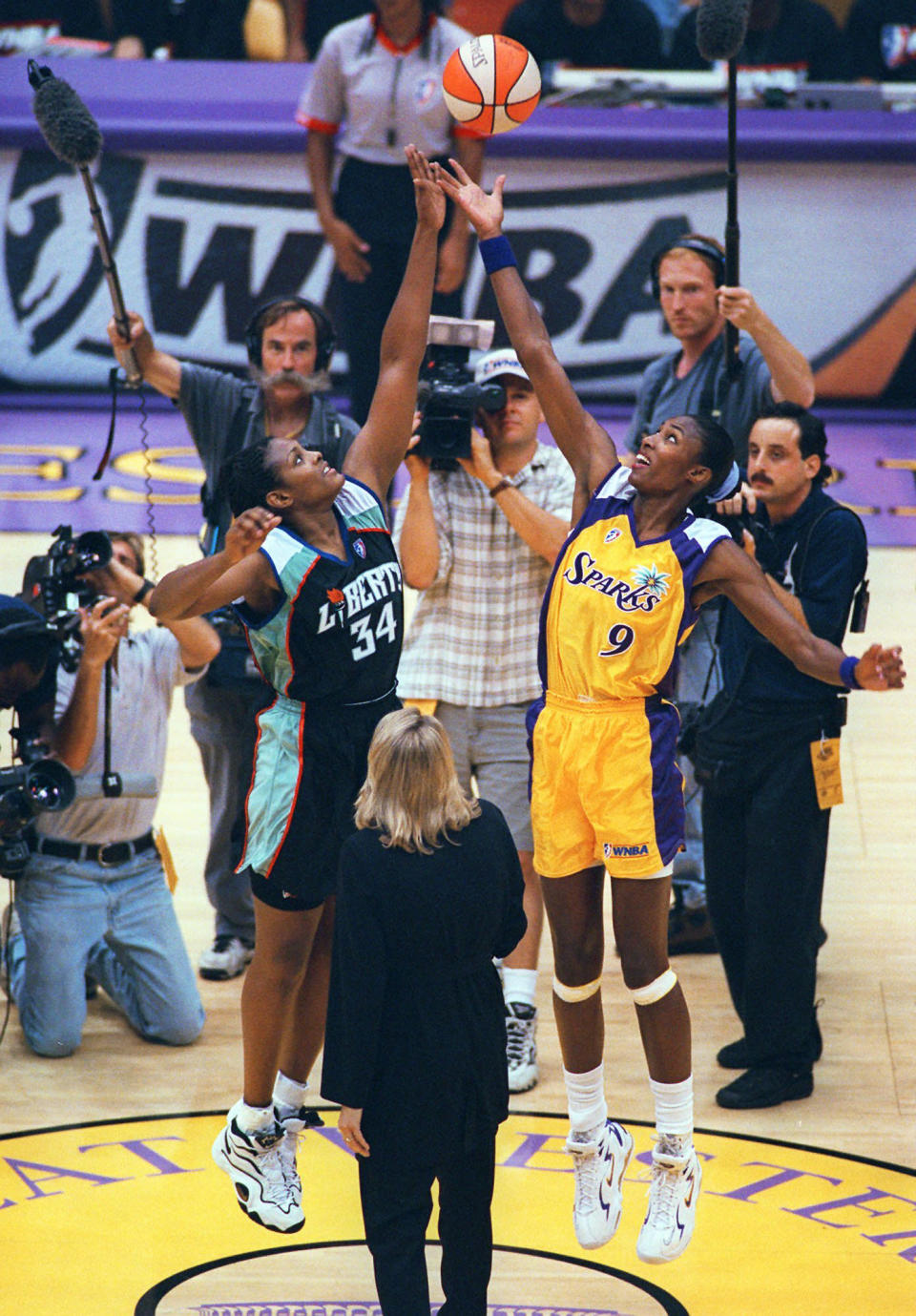 """FILE - In this June 21, 1997, file photo, Los Angeles Sparks' Lisa Leslie, right, and New York Liberty's Kym Hampton leap for the ball during the opening tip of the inaugural WNBA basketball at the Forum in Inglewood, Calif. Hampton and Sue Wicks are """"Liberty Legends,"""" who have worked in the New York basketball community for years. (AP Photo/Michael Caulfield, File)"""