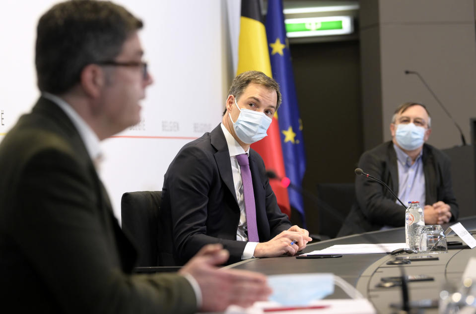 Belgium's Prime Minister Alexander De Croo, center, attends a media conference with Belgium's virologist Steven Van Gucht and Dr. Yves Van Laethem at the prime minister's office in Brussels, Monday, Feb. 22, 2021. The government on Monday presented scientific projections of the spread of the COVID-19 pandemic in Belgium, indicating it would be very risky to extensively loosen the current restrictions over the coming weeks. (Philip Reynaers, Pool via AP)