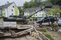 An armoured engineer vehicle of the German forces lifts a damaged car during the clean-up work of the severe storm damage in Hagen, Germany, Friday, July 16, 2021. Heavy rains caused mudslides and flooding in the western part of Germany. Multiple have died and dozens are missing as severe flooding in Germany and Belgium turned streams and streets into raging, debris-filled torrents that swept away cars and toppled houses. (Julian Stratenschulte/dpa via AP)