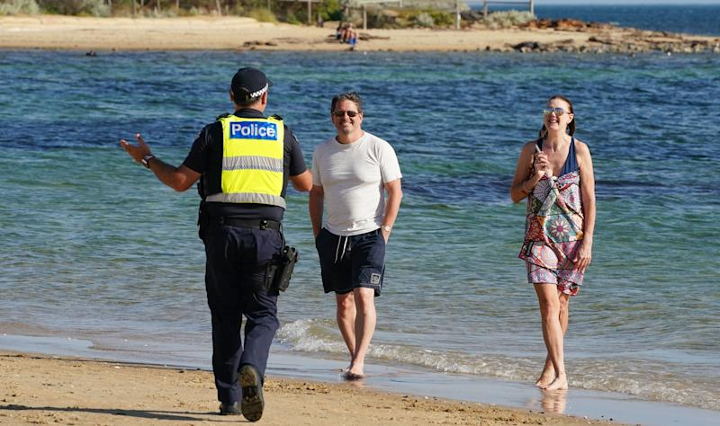 Police officers inform beachgoers that the beach is closed at Brighton Beach in Melbourne. Source: AAP