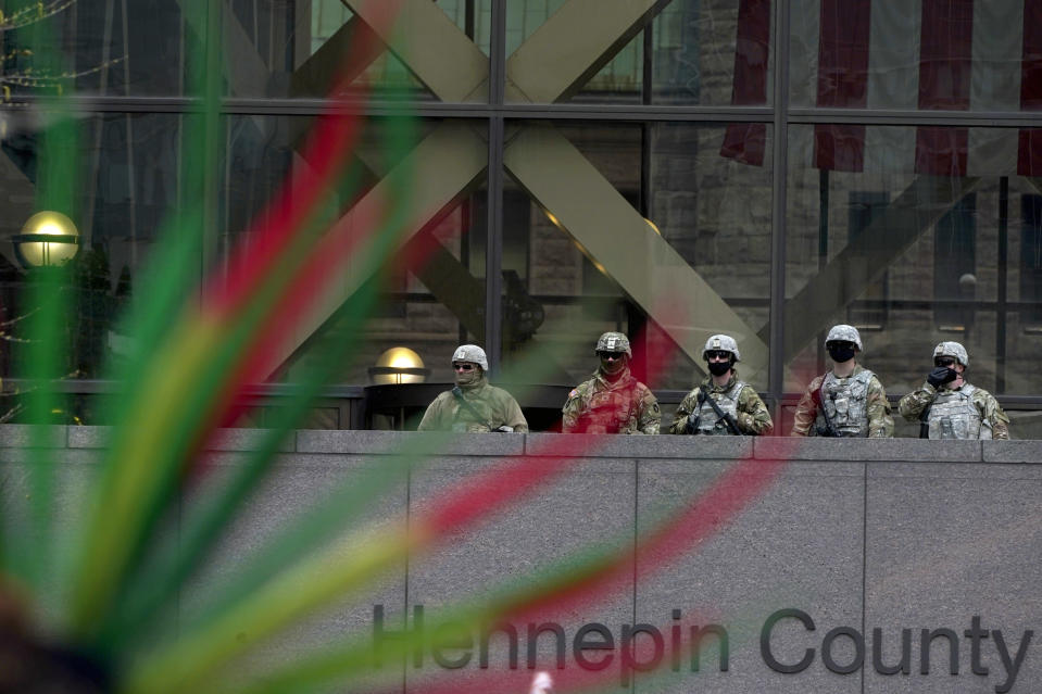 National Guard members are seen through the hair dress of an Indigenous person during a rally outside of the Hennepin County Government Center in Minneapolis on Monday, April 19, 2021, after the murder trial against former Minneapolis police Officer Derek Chauvin advanced to jury deliberations. (AP Photo/Julio Cortez)