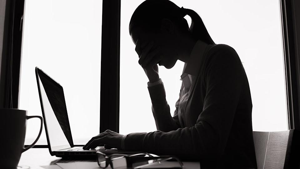 Picture of a silhouette of a woman, looking at. her laptop. Image based abuse reports have risen amid the coronavirus lockdown