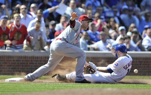Chicago Cubs' Nate Schierholtz, right, slides safely into third as Cincinnati Reds' Todd Frazier waits for the ball after hitting a triple during the sixth inning of a baseball game on Thursday, June 13, 2013, in Chicago. (AP Photo/Jim Prisching)