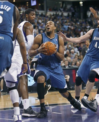 Minnesota Timberwolves forward Derrick Williams, center, drives into the lane against Sacramento Kings defender Jason Thompson, left, during the first half of an NBA basketball game in Sacramento, Calif., Sunday, March 18, 2012. (AP Photo/Steve Yeater)