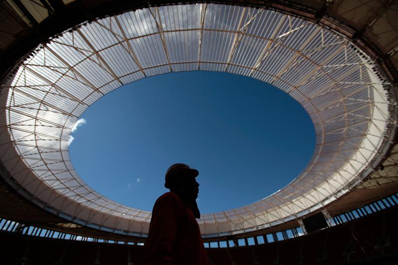 FILE - In this May 14, 2013 file photo, an employee stand inside the National Stadium Mane Garrincha in Brasilia, Brazil. The action at the Confederations Cup will be going from the nation's capital to the coastal cities in the northeast to the beaches of Rio de Janeiro. Six cities will stage matches at the World Cup warm-up tournament from June 15-30, with the capital of Brasilia hosting the opener in a new stadium and the renovated Maracana Stadium holding the final on June 30. (AP Photo/Eraldo Peres, File)