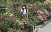 A woman wearing a face mask to protect against the spread of the new coronavirus visits a botanical garden in Tokyo, Monday, Aug, 10, 2020. (AP Photo/Koji Sasahara)