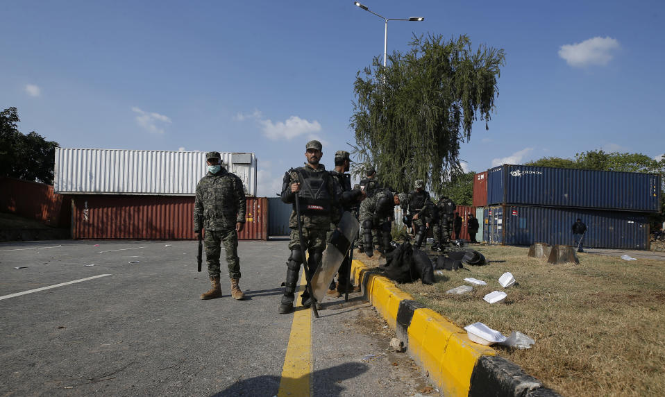 Paramilitary soldiers stand guard beside shipping containers placed by authorities on a highway to stop supporters of 'Tehreek-e-Labaik Pakistan, a religious political party, entering into the capital during an anti-France rally in Islamabad, Pakistan, Monday, Nov. 16, 2020. The supporters are protesting the French President Emmanuel Macron over his recent statements and the republishing in France of caricatures of the Muslim Prophet Muhammad they deem blasphemous. (AP Photo/Anjum Naveed)