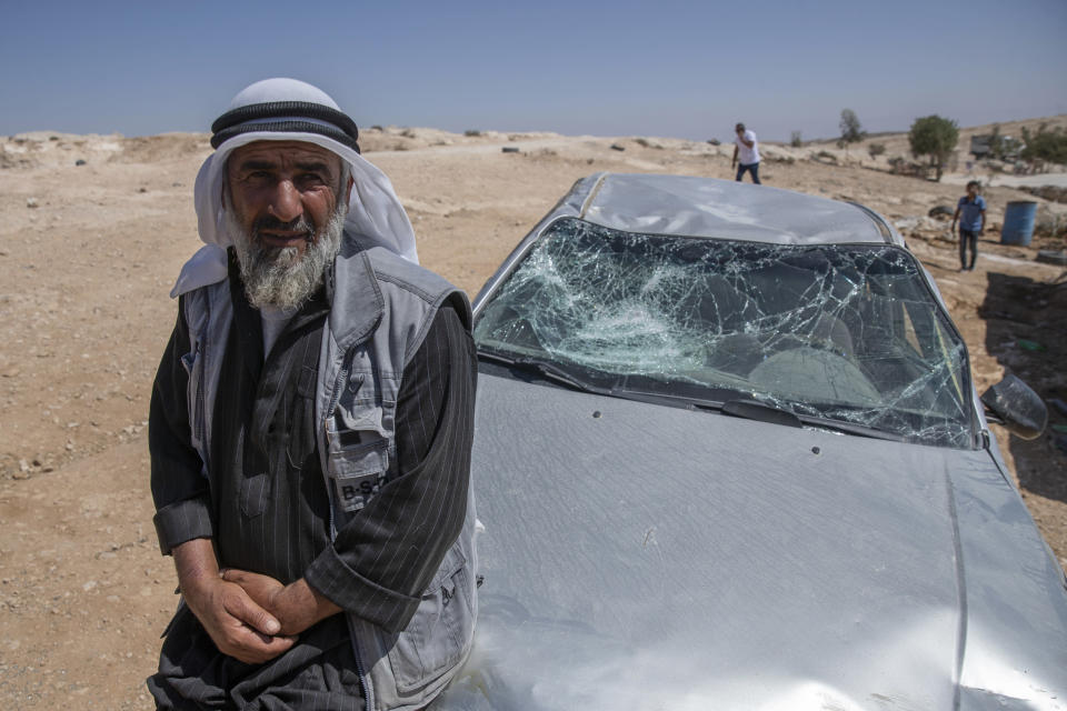 A Palestinian man leans on his smashed vehicle following a settlers attack from nearby settlement outposts on his Bedouin community, in the West Bank village of al-Mufagara, near Hebron, Thursday, Sept. 30, 2021. An Israeli settler attack last week damaged much of the village's fragile infrastructure. (AP Photo/Nasser Nasser)