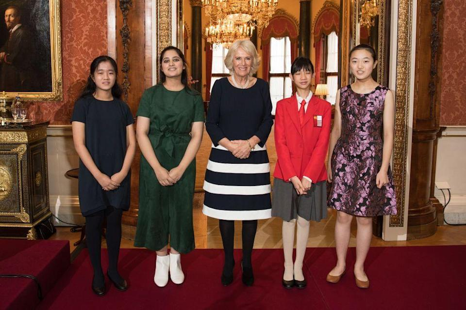 <p>Camilla Parker Bowles wore a striped navy and white dress and pearl necklace for a reception at Buckingham Palace for winners of the Queen's Commonwealth Essay Competition. </p>