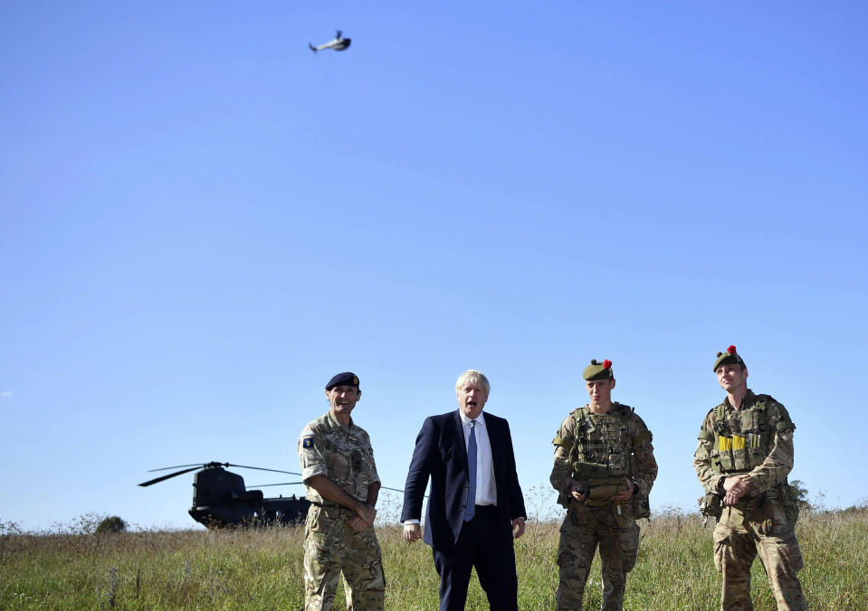 """Britain's Prime Minister Boris Johnson flies a Black Hornet nano drone as he meets with military personnel on Salisbury Plain training area near Salisbury, England, Thursday, Sept. 19, 2019. British Prime Minister Boris Johnson was accused by a one of the country's former leaders of a """"conspicuous"""" failure to explain why he suspended Parliament for five weeks, as a landmark Brexit case at the U.K. Supreme Court came to a head on Thursday. (Ben Stansall/Pool Photo via AP)"""