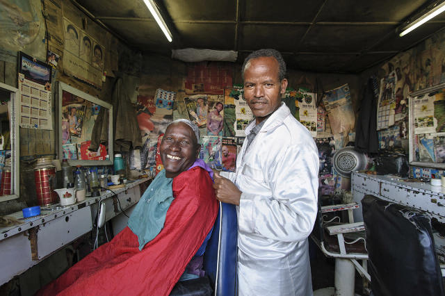 <p>A barber and his client pause and smile for a photo at barbershop in Addis Ababa. </p>