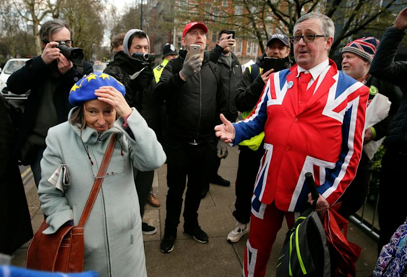 An anti-Brexit, left, and pro-Brexit supporter debate outside Parliament in London on March 12, 2019.