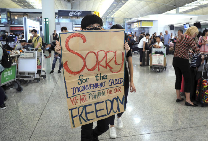 A protester shows a placard to stranded travelers during a demonstration at the Airport in Hong Kong, Tuesday, Aug. 13, 2019. (Photo: Kin Cheung/AP)