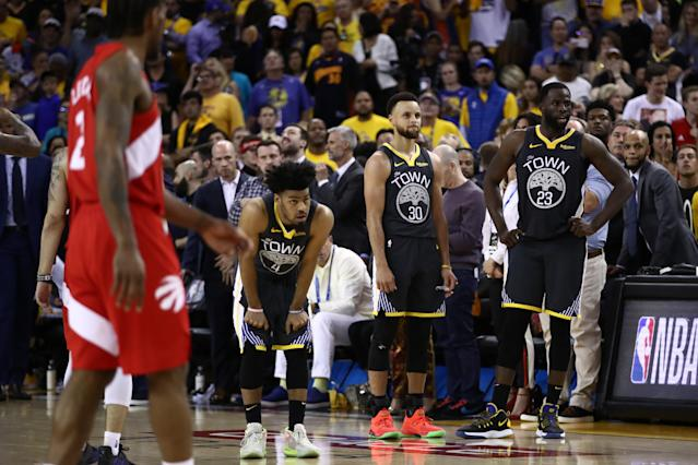 Quinn Cook (4), Stephen Curry (30) and Draymond Green (23) of the Golden State Warriors react late in their Game 6 loss against the Toronto Raptors. (Getty)