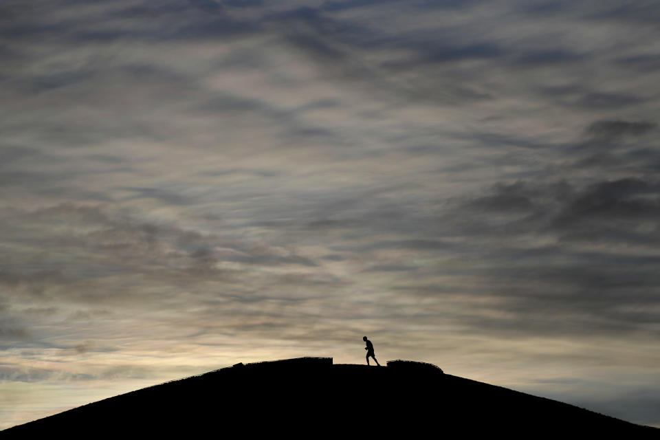 A jogger takes an early morning run as lockdown measures start to be lifted in London, Tuesday, April 6, 2021. Temperatures dropped to -7C (19.4F) in some parts of the UK overnight as Arctic winds brought an end to the good weather. (AP Photo/Kirsty Wigglesworth)