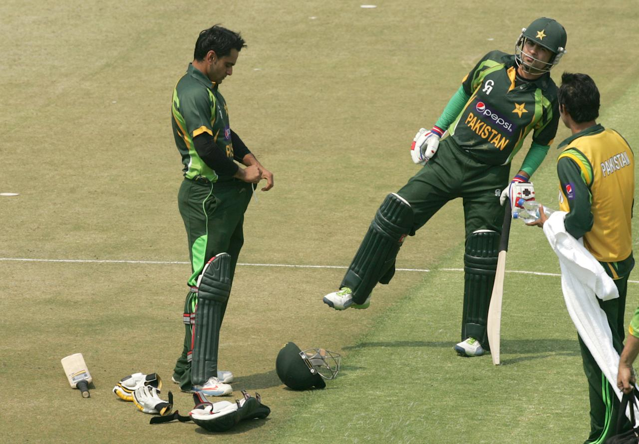 Pakistan batsman Muhammad Hafeez (L) with team mate Ahmed Shehzad (R) tucks in after receiving treatment for a hamstring injury during the final game of the three match ODI cricket series between Pakistan and Zimbabwe at the Harare Sports Club August 31, 2013. AFP PHOTO / JEKESAI NJIKIZANA        (Photo credit should read JEKESAI NJIKIZANA/AFP/Getty Images)