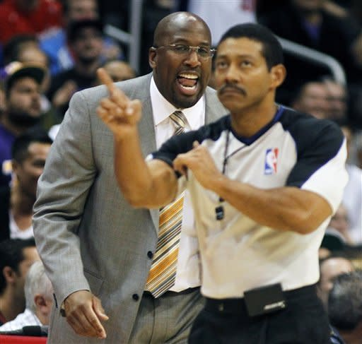 Los Angeles Lakers head coach Mike Brown, left, yells at umpire Angel Hernandez (55) for calling an offensive foul against his team playing against the Los Angeles Clippers during the first half of an NBA preseason basketball game in Los Angeles, Wednesday, Dec. 21, 2011. (AP Photo/Alex Gallardo)