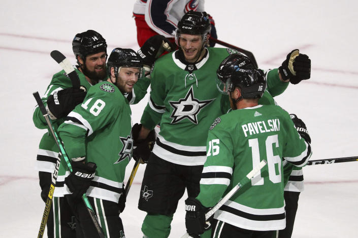 The Dallas Stars, including Jamie Benn (14), Jason Dickinson (18), Jamie Oleksiak (2) and Joe Pavelski (16) celebrate a second-period goal by Miro Heiskanen (4) against the Columbus Blue Jackets during an NHL hockey game on Thursday, April 15, 2021, in Dallas. (AP Photo/Richard W. Rodriguez)