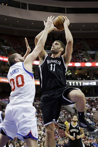 Brooklyn Nets' Brook Lopez (11) shoots as Philadelphia 76ers' Spencer Hawes (00) defends in the first half of an NBA basketball game, Monday, March 11, 2013, in Philadelphia. (AP Photo/Matt Slocum)