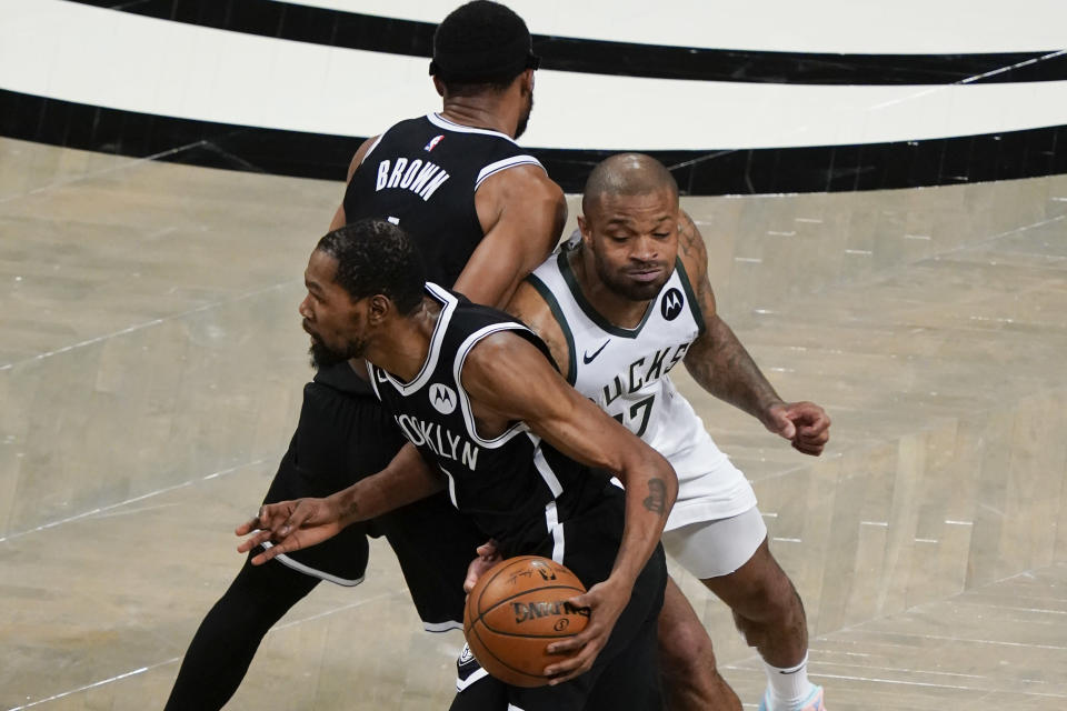 Milwaukee Bucks' P.J. Tucker (17) fights through a pick set by Brooklyn Nets' Bruce Brown, top left, to defend against Kevin Durant, bottom left, during the first half of Game 7 of a second-round NBA basketball playoff series Saturday, June 19, 2021, in New York. (AP Photo/Frank Franklin II)