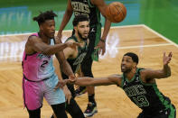 Miami Heat's Gabe Vincent, left, passes the ball as Boston Celtics' Jayson Tatum, center, and Tristan Thompson, right, try to block in the first half of a basketball game, Sunday, May 9, 2021, in Boston. (AP Photo/Steven Senne)
