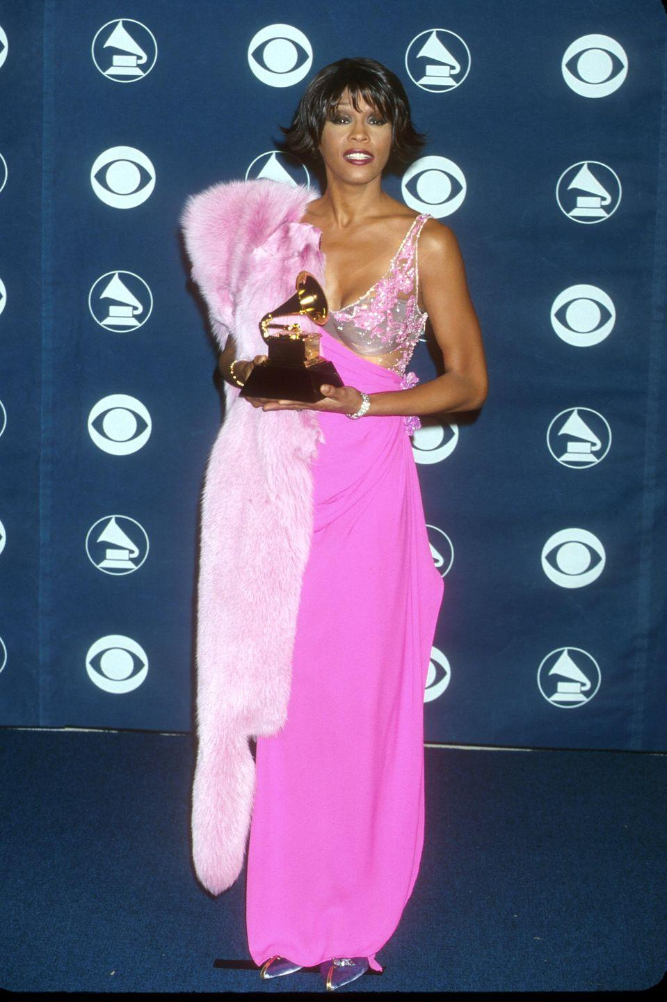 <p>Whitney looked DIVINE in her pink floor-length gown with a sheer top and a fuzzy baby pink jacket draped over her shoulder.</p>