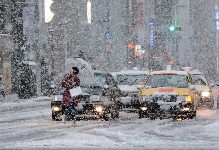 A pedestrian crosses the road in the snow in Tokyo on January 14, 2013. The winter's first snowfall blanketed the Japanese capital and its environs, paralysing traffic and stranding young people taking part in traditional coming-of-age ceremonies