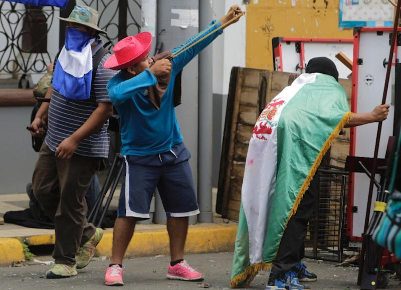 Demonstrators stand behind an improvised barricade during clashes with riot police in Masaya, Nicaragua (AFP Photo/INTI OCON)