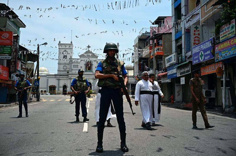 Priests walk on a blocked street as soldiers stand guard outside St. Anthony's Shrine in Colombo (Getty)