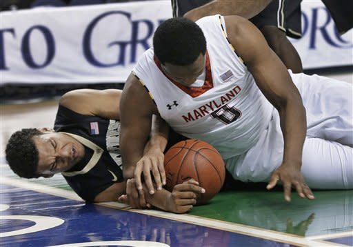 Wake Forest's Devin Thomas, left, and Maryland's Charles Mitchell, right, vie for control of a loose ball during the first half of an NCAA college basketball game at the Atlantic Coast Conference men's tournament in Greensboro, N.C., Thursday, March 14, 2013. (AP Photo/Gerry Broome)