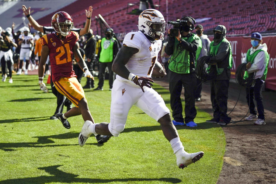Arizona State running back Chip Trayanum (1) scores a touchdown ahead of Southern California safety Isaiah Pola-Mao (21) during the first half of an NCAA college football game Saturday, Nov. 7, 2020, in Los Angeles. (AP Photo/Ashley Landis)