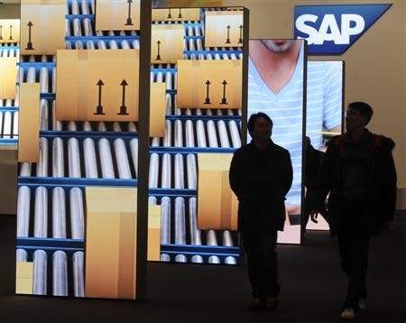 People are pictured beside screens at the booth of German company SAP during preparations at the CeBit computer fair in Hanover in this March, 4, 2012 file picture. REUTERS/Fabian Bimmer