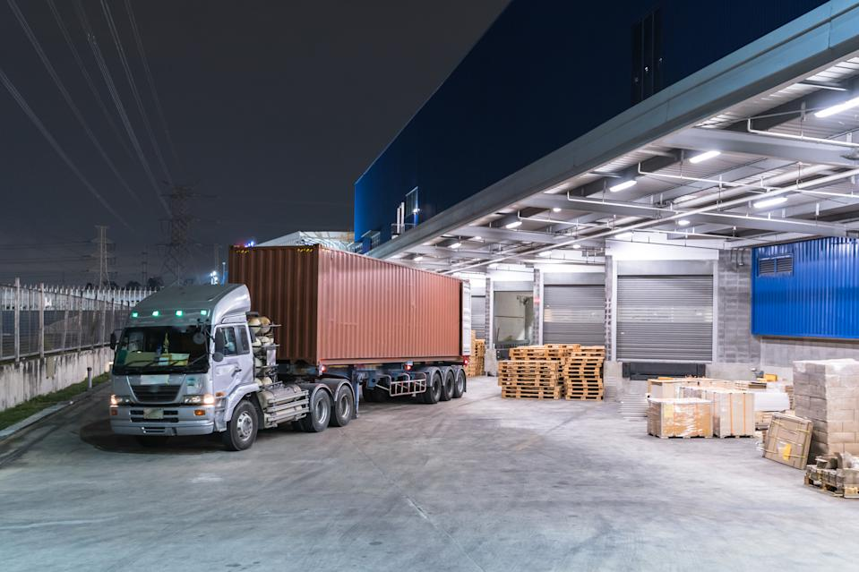 Truck is carrying container is parking in front warehouse at night time