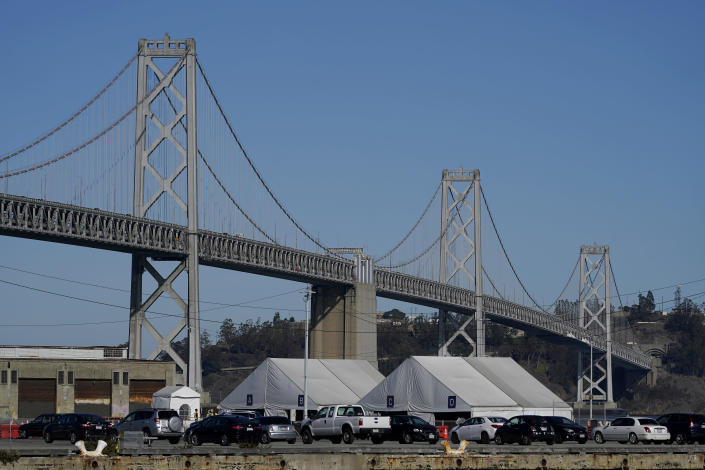 Tents from the CityTestSF at Pier 30/32 COVID-19 testing site sit in front of the San Francisco-Oakland Bay Bridge during the coronavirus pandemic in San Francisco, Wednesday, Dec. 23, 2020. (AP Photo/Jeff Chiu)