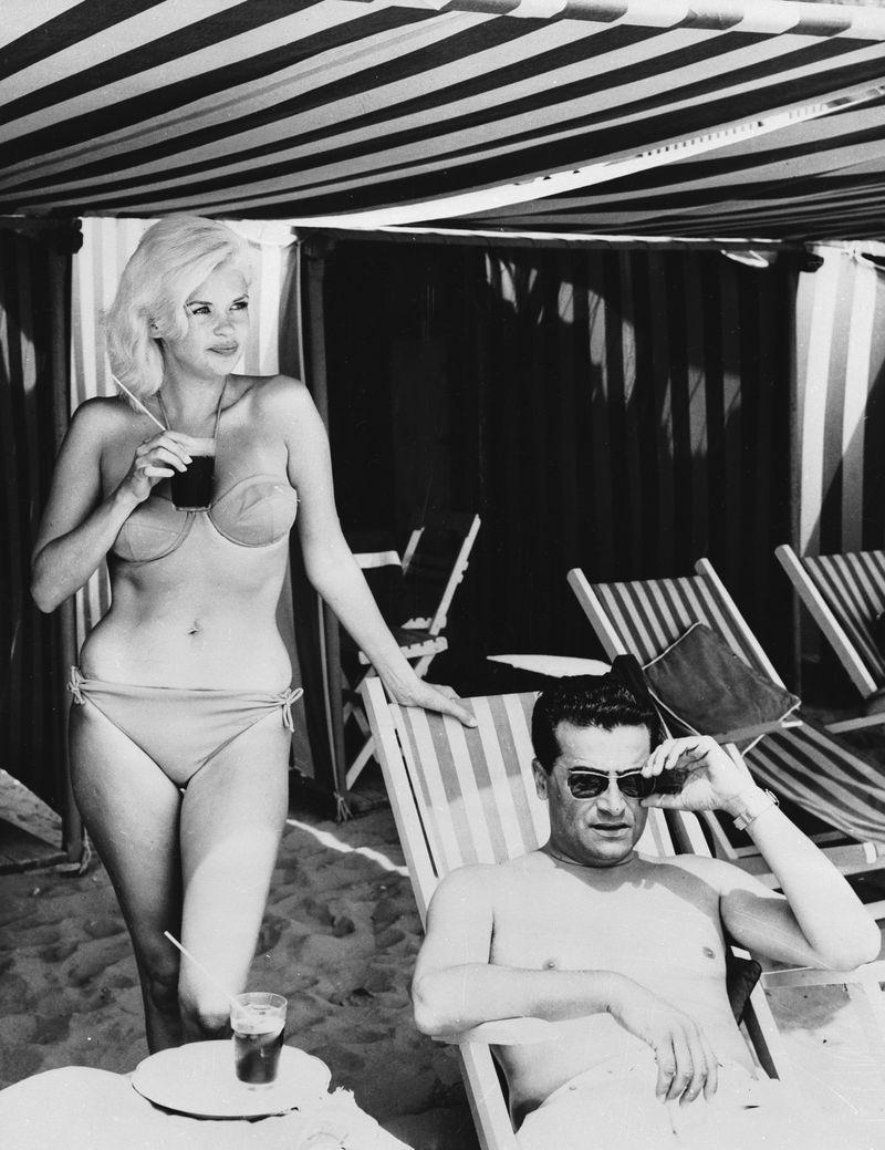 <p>Jayne Mansfield shows off her figure in a strapless bikini as she and film producer, Enrico Bomba, vacation in Lido Beach in 1962.</p>
