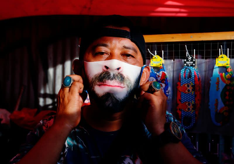 A man wears a face design mask at a traditional market to prevent the spread of the coronavirus disease (COVID-19) outbreak in Jakarta