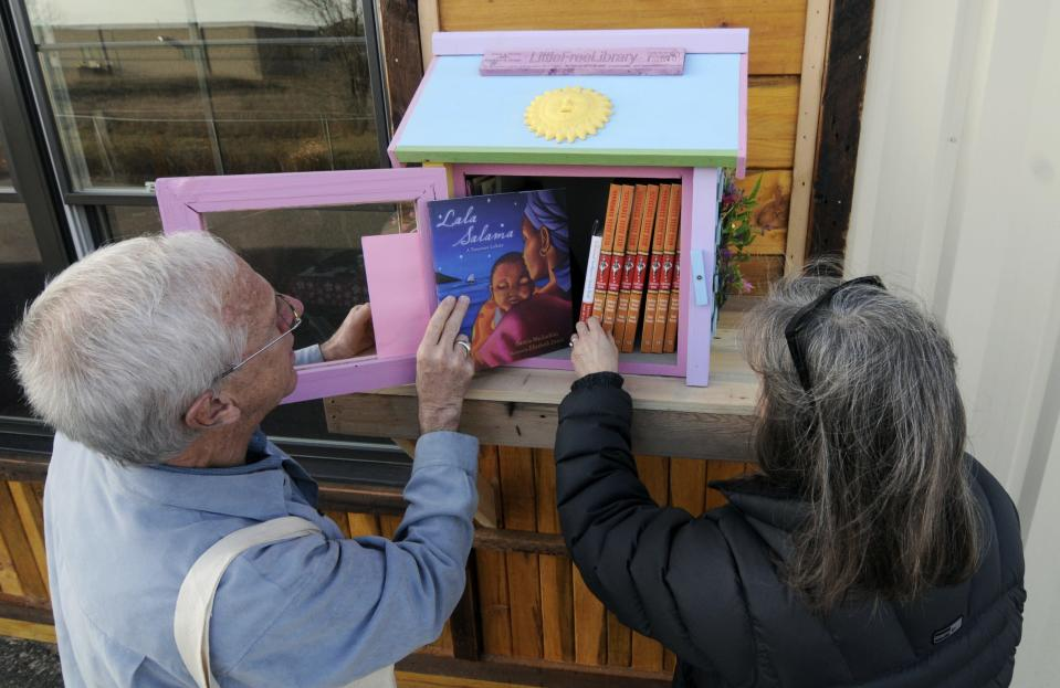 In this Thursday, Dec. 6, 2012 photo, Rick Brooks, left, looks through the small glass door as he and Elizabeth Kennedy pose beside one of the Little Free Libraries lending boxes, in Hudson, Wis. The non-profit Little Free Libraries movement is branching out in new directions including inner-city neighborhoods where kids might not have many books and into developing countries were people are hungry for reading material and by Christmas expects its followers will have erected over 5,000 book boxes across the U.S. alone. Brooks is co-founder of Little Free Libraries. (AP Photo/Jim Mone)
