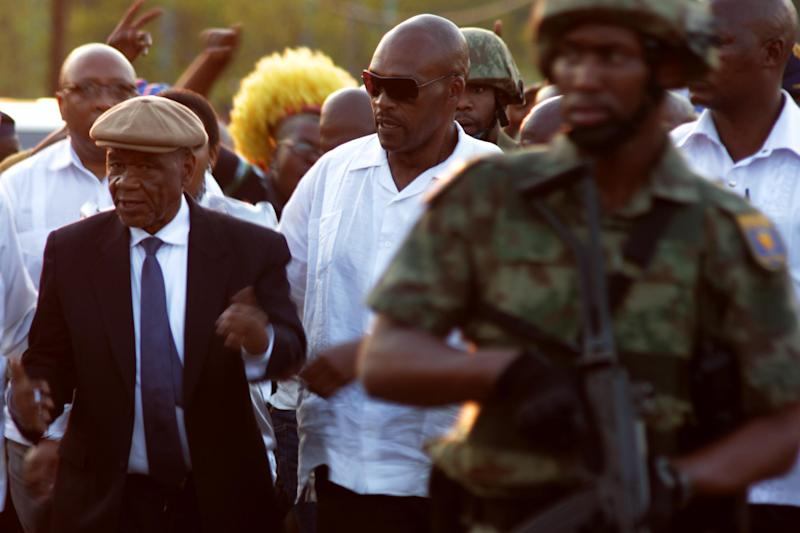 Lesotho Prime Minister Tom Thabane (L) arrives at Maseru border gate under heavy security on September 16 2014 (AFP Photo/Hlompho Letsielo)