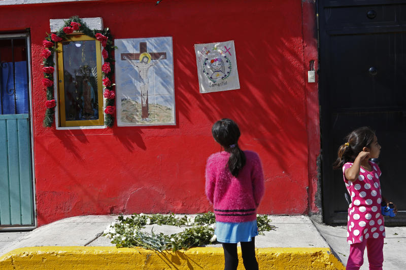 """Girls look at a home where an embroidery reading """"Samantha"""" hangs next to an image of Jesus and Or Lady of Guadalupe, during a vigil by activists from the """"Women from the Periphery for the Periphery Collective"""" honoring 2-year-old Samantha who was found dead in June, as the group protests femicide in Ecatepec, Mexico, Sunday, Oct. 6, 2019. The collective of activists and the relatives of murdered females visited four sites where females were found dead in Ecatepec, in the state of Mexico where authorities declared in 2015 an alert concerning gender violence against women. (AP Photo/Ginnette Riquelme)"""