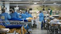 Health workers care for patients infected with COVID-19 at the full emergency room in a hospital in southern Brazil