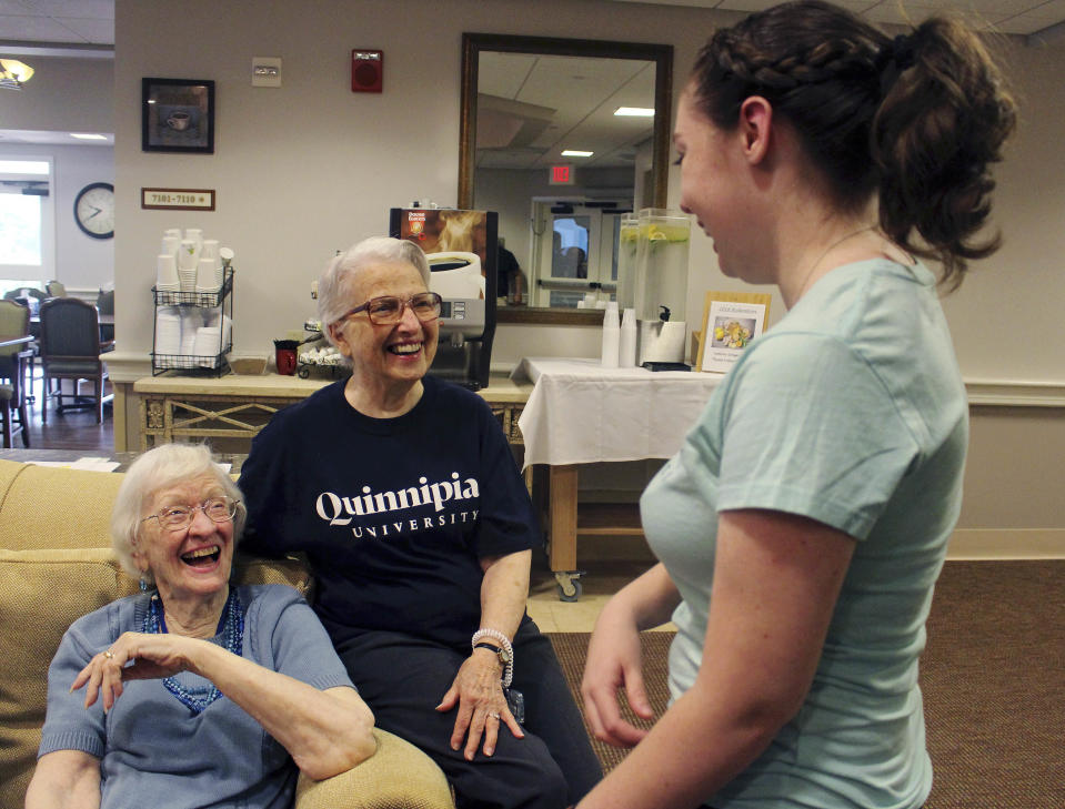 Cathleen Dacey, right, a Quinnipiac University law student, talks to Jeanne Piccirillo, 90, and Cairisse Miessau, 85, at Masonicare at Ashlar Village, a retirement community in Wallingford, Conn. Dacey will live at the center this school year as part of an intergenerational learning program. (AP Photo/Pat Eaton-Robb)