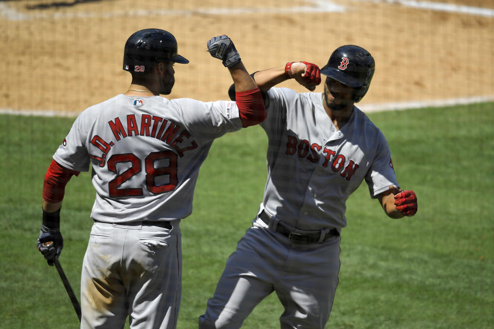 CORRECTS TO A TWO RUN HOME RUN NOT SOLO Boston Red Sox's Xander Bogaerts, right, is congratulated by J.D. Martinez after hitting a two-run home run during the third inning of a baseball game against the Los Angeles Angels Sunday, Sept. 1, 2019, in Anaheim, Calif. (AP Photo/Mark J. Terrill)